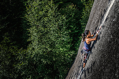 Female rock climber, climbing granite rock (The Chief), elevated view, Squamish, Canada - p429m1578424 by Alex Eggermont