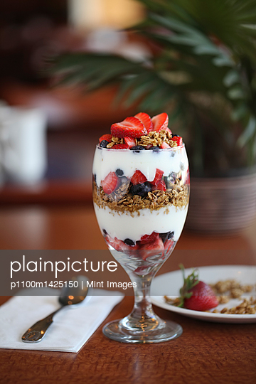 A dessert of yoghurt, strawberries, and blueberries layered in a wine glass on a table.