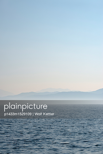The mountains of the Greek Epirus region in delicate morning light seen from the Ionian sea. - p1433m1529109 by Wolf Kettler