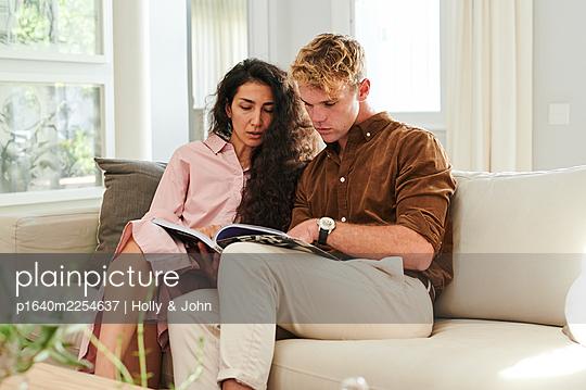 Paar auf der Couch betrachtet ein Magazin - p1640m2254637 von Holly & John