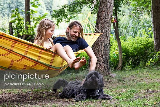 Father and daughter playing with dog - p294m2206274 by Paolo
