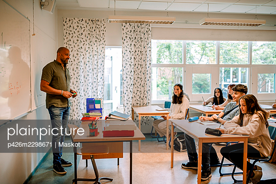 Male professor teaching to student in classroom - p426m2298671 by Maskot
