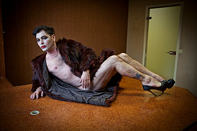Drag queen sitting on the boss's desk - p1513m2043987 by ESTELLE FENECH