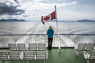 BRITISH COLUMBIA, CANADA. A woman looks over railing at stern of ferry boat with Canadian flag above her head and water and mountains in distance. - p343m1218050 by David Hanson