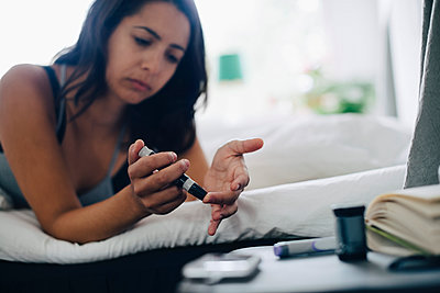 Woman checking blood sugar level while lying in bedroom - p426m1537143 by Maskot