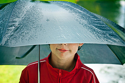 Boy under an umbrella - p924m699192f by Mieke Dalle