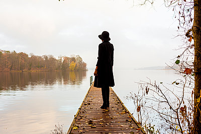 Young woman with hat on boardwalk by the lake - p975m2228196 by Hayden Verry