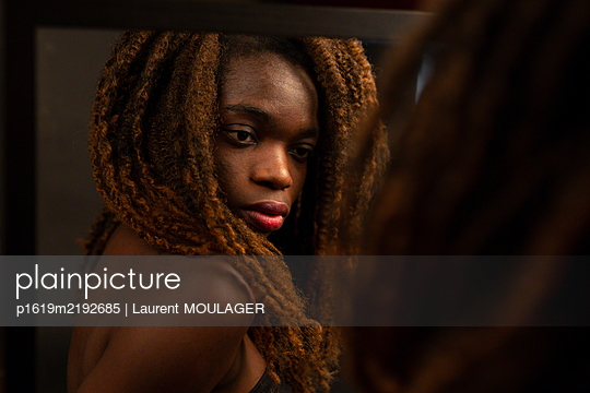 Portrait of a young black woman with braided hair looking at herself in a mirror  - p1619m2192685 by Laurent MOULAGER