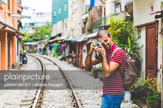 Vietnam, Hanoi, man in the city taking a picture with an old-fashioned camera - p300m1581371 von William Perugini