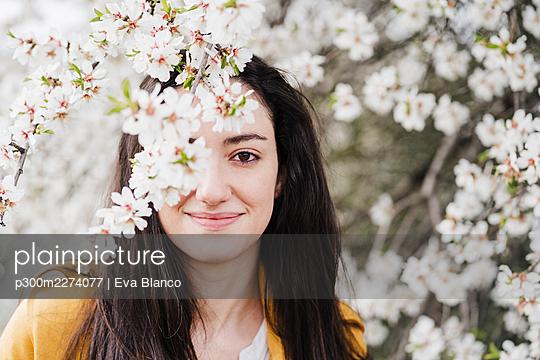 Smiling woman seen through flowers during springtime - p300m2274077 by Eva Blanco