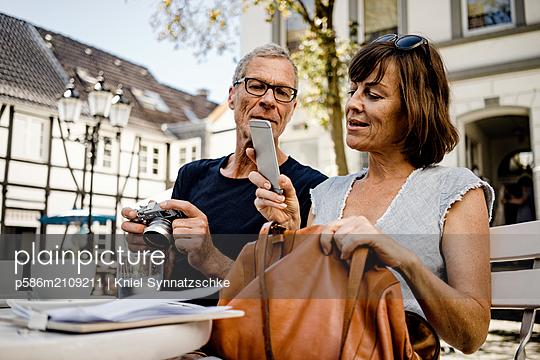 Mature couple using smartphone in sidewalk cafe - p586m2109211 by Kniel Synnatzschke