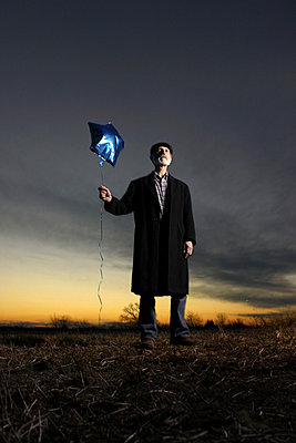Man with blue balloon - p1019m739800 by Stephen Carroll