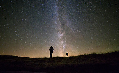 Friends standing against star field at night - p1166m1096152f by Cavan Images