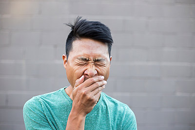Close-up of man with hands covering mouth while yawning against wall - p1166m2025311 by Cavan Images