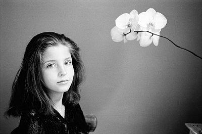 Teenage girl alongside flowering branch - p1648m2244819 by KOLETZKI