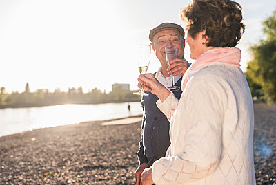 Senior couple toasting with sparkling wine at sunset - p300m1460658 by Uwe Umstätter