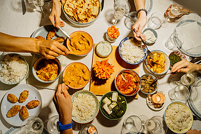Hands of people dining together around table set with Indian food - p300m2202427 by VITTA GALLERY