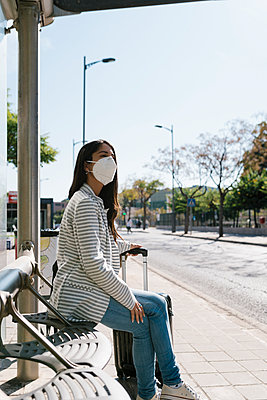 Woman waiting for bus on sunny day during COVID-19 pandemic - p300m2240323 by Ezequiel Giménez