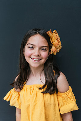 Smiling girl wearing yellow top and headband standing against black background - p300m2251060 by MORNINGVIEW AGENCY