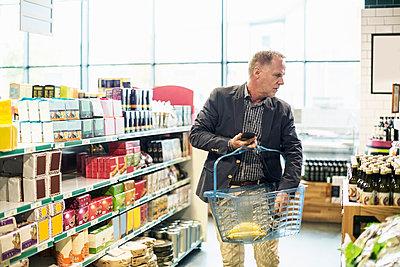 Mature man buying groceries in supermarket - p426m1407399 by Kentaroo Tryman