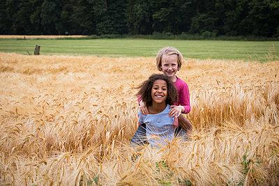 Kinder spielen auf Feld mit Gerste - p471m2022071 von CLMasur