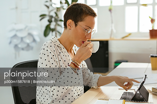 Woman drinking coffee and using tablet at desk in office - p300m1587618 von Bonninstudio