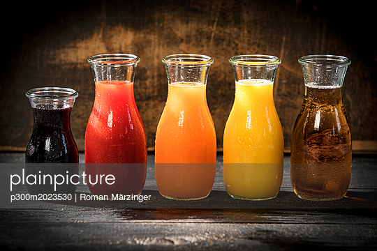 Row of five glass bottles of various fruit juices - p300m2023530 by Roman Märzinger