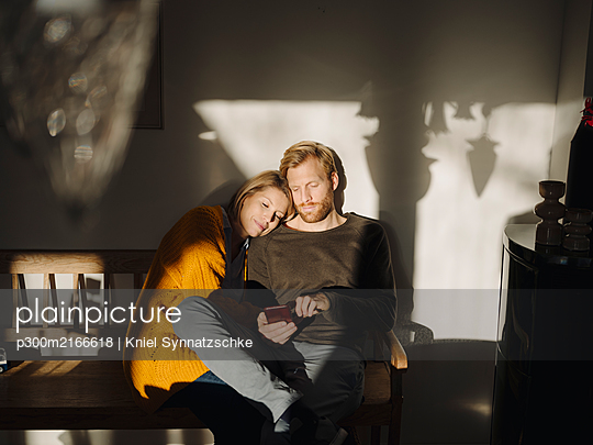 Relaxed couple sitting on bench in sunlight at home with man using cell phone - p300m2166618 von Kniel Synnatzschke