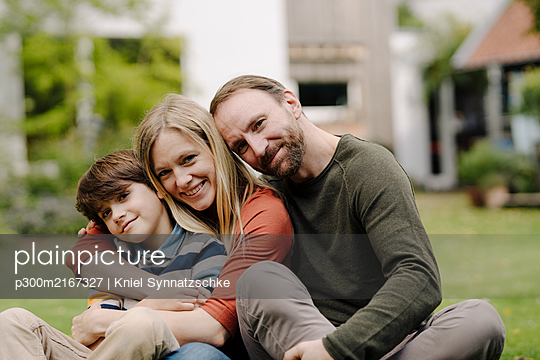 Happy family sitting on grass in their garden - p300m2167327 by Kniel Synnatzschke