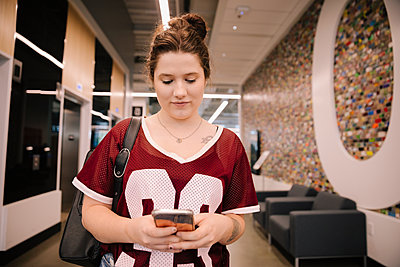 Student using smartphone in corridor - p1192m2110304 by Hero Images