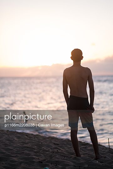 teenage boy watching the sunset on the north shore of oahu - p1166m2208038 by Cavan Images