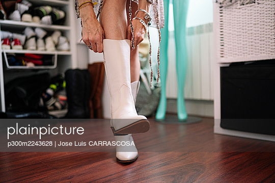 Woman wearing new white boot in apartment - p300m2243628 by Jose Luis CARRASCOSA