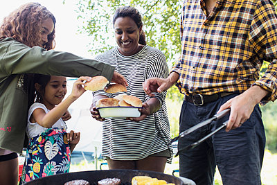 Family barbecuing hamburgers - p1023m2066704 by Sam Edwards