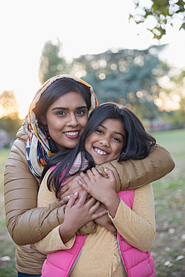Portrait happy Muslim mother in hijab hugging daughter in park - p1023m2087935 by Tom Merton