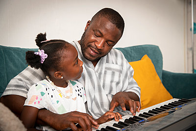 Affectionate father and daughter playing keyboard piano on sofa - p1023m2238484 by Himalayan Pics