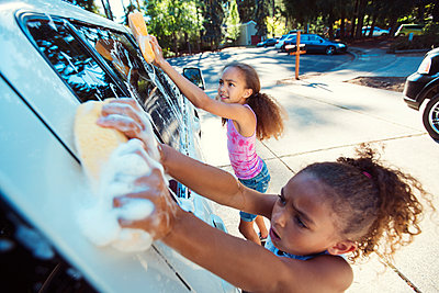 High angle view of girls washing car in driveway - p1166m1225976 by Cavan Images