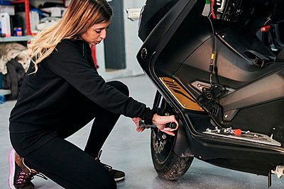 A woman works in an auto repair shop fixing a motorcycle - p1166m2268335 by Cavan Images