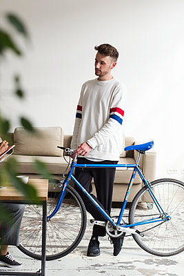 Szenetyp auf Fahrrad in einem modernen Büro  - p1301m2021062 von Delia Baum