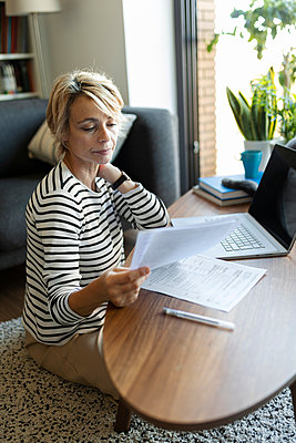 Mature woman with documents using laptop at home - p300m2144778 by Valentina Barreto
