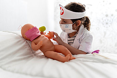 Girl in doctor's costume caring of her doll with a mask - p300m2198073 by Ezequiel Giménez