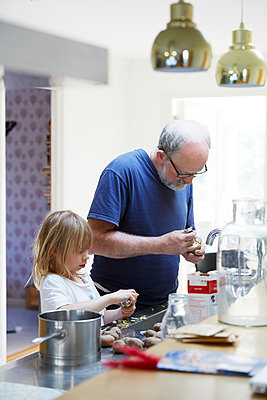Grandfather and granddaughter preparing food - p312m1229112 by Anna Kern