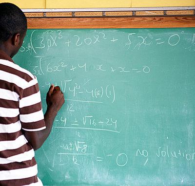Teen boy writing on chalkboard - p3721885 by James Godman
