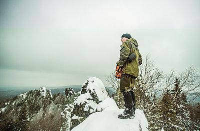 Caucasian hiker standing on snowy hilltop - p555m1414461 by Aleksander Rubtsov