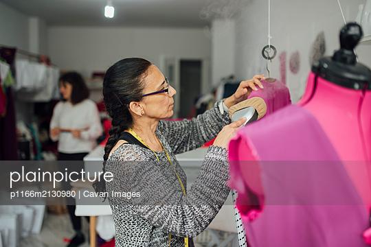 senior woman working in a sewing workshop - p1166m2130980 by Cavan Images