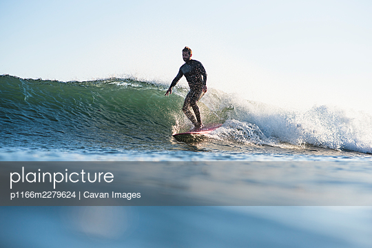 Athletic Man Surfing a wave during summer sunset - p1166m2279624 by Cavan Images