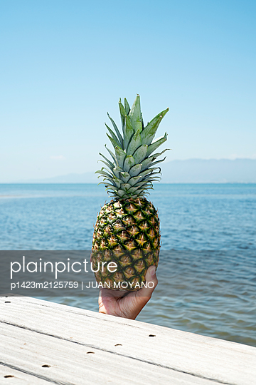 Man with a pineapple in his hand in a pier - p1423m2125759 by JUAN MOYANO