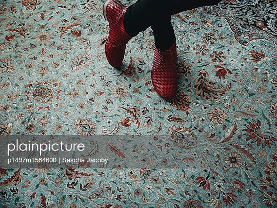 Jungs Frau mit roten Schuhen auf orientalischem Teppich - p1497m1584600 von Sascha Jacoby
