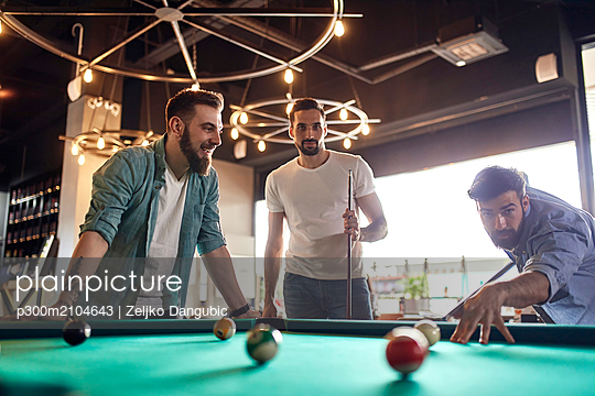 Friends playing billiards together - p300m2104643 by Zeljko Dangubic