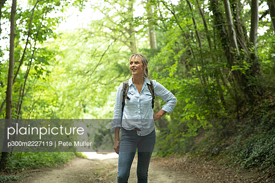 Senior woman with hand on hip looking away while exploring in forest - p300m2227119 by Pete Muller