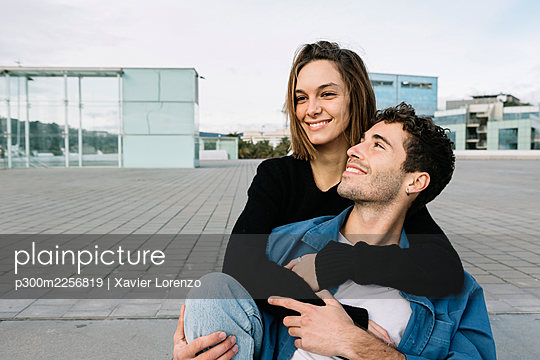 Smiling couple embracing in city - p300m2256819 by Xavier Lorenzo
